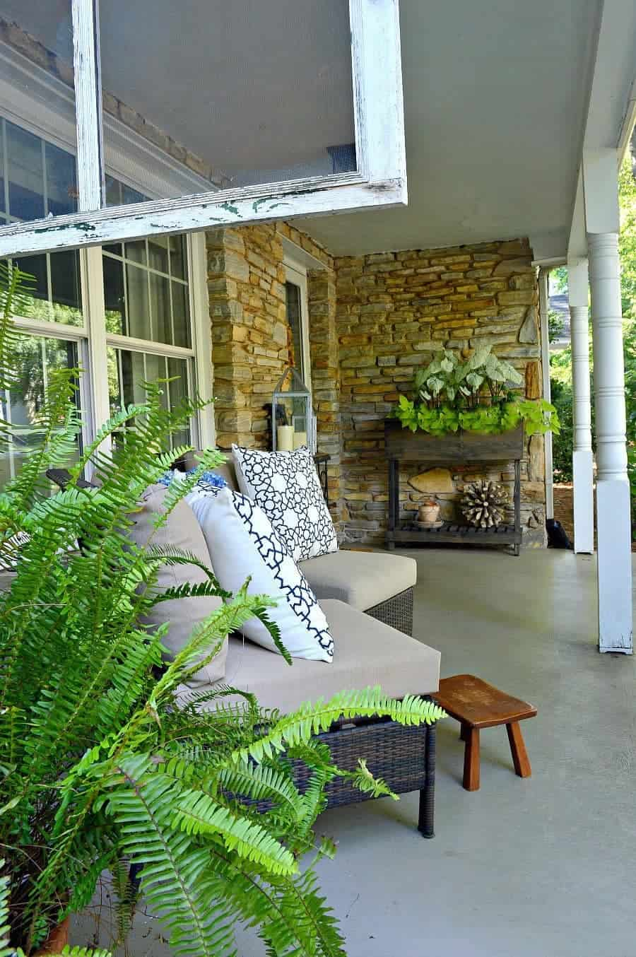 two wicker chairs on porch with blue and white pillows, a little footstool and a green potted fern