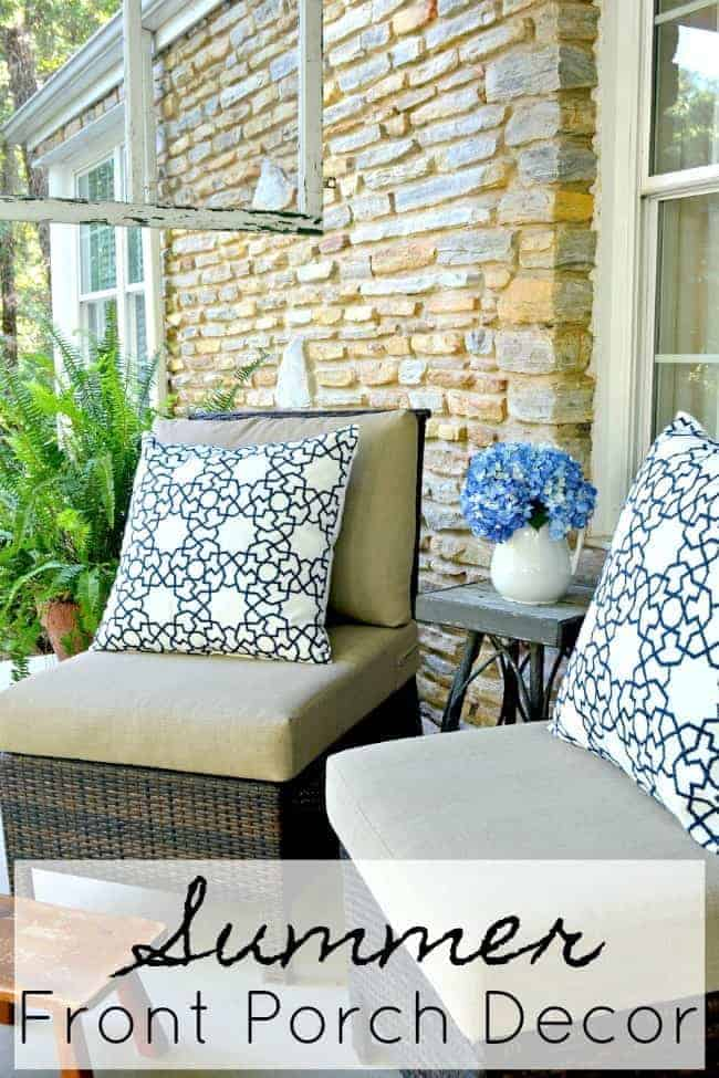 two wicker chairs on covered porch with blue and white pillows, a little footstool and a hanging screen window