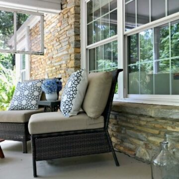 A front porch with furniture and a large window