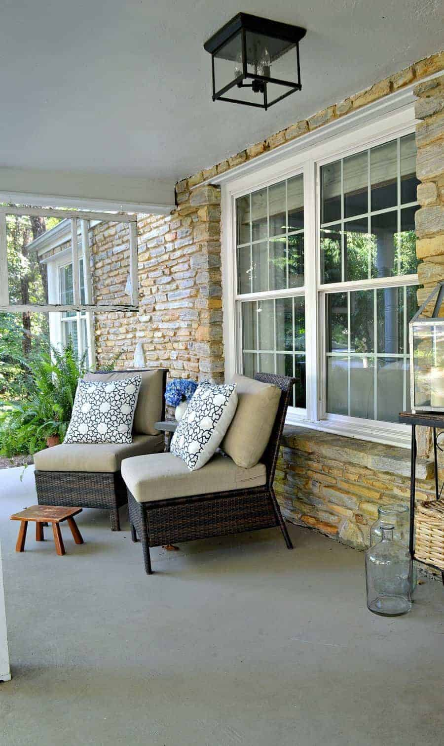 covered front porch with 2 wicker chairs and blue and white pillows