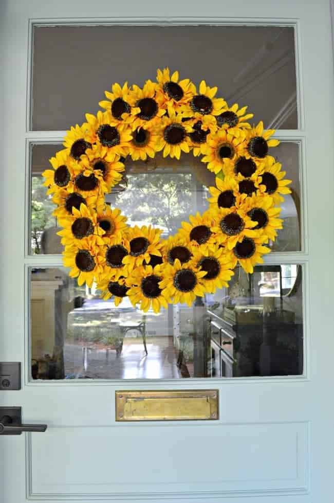 sunflower wreath hanging on blue front door