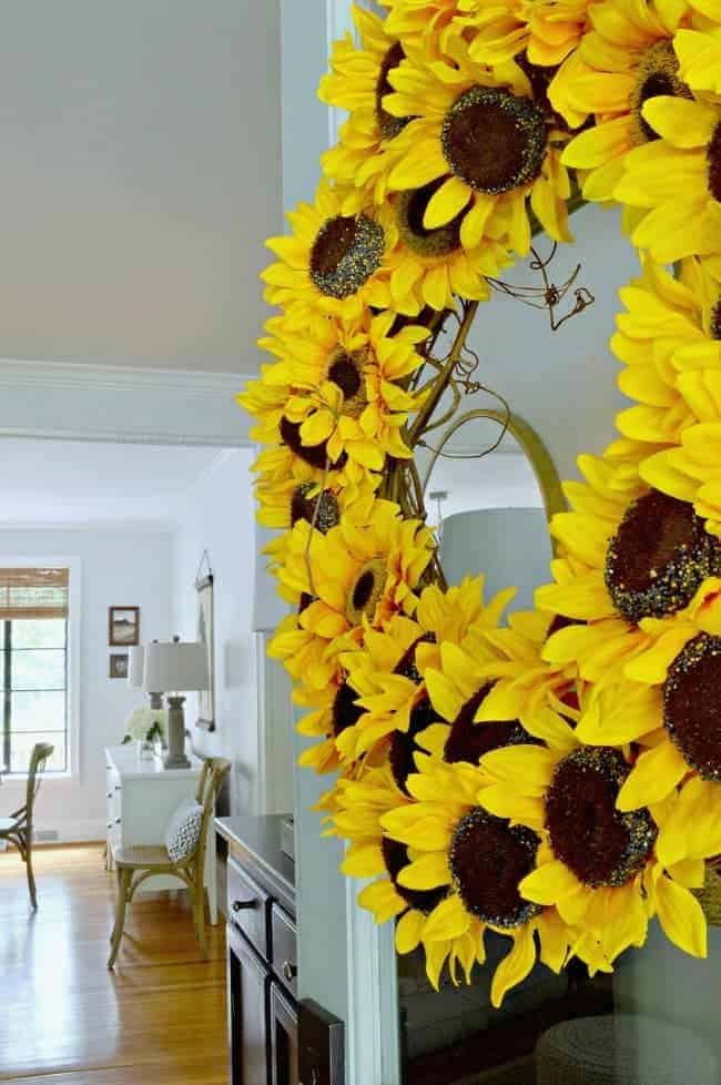 sunflower wreath hanging on front door with view into dining room for Cottage Musings