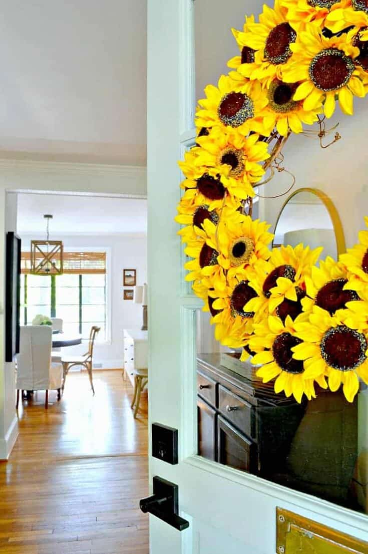 sunflower wreath hanging on turquoise front door with a view into a house