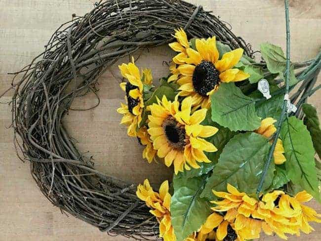 craft supplies of sunflowers and grapevine wreath for a How to Make a Sunflower Wreath tutorial