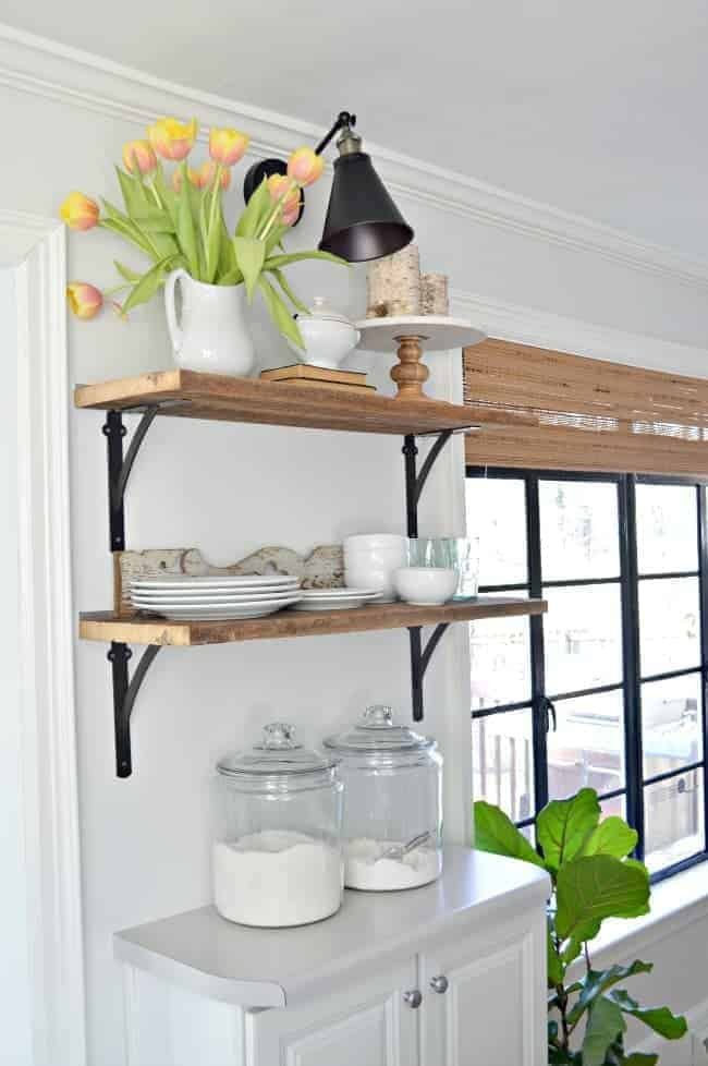 DIY wireless wall sconce hanging over open shelving in kitchen with a pitcher of tulips on top shelf