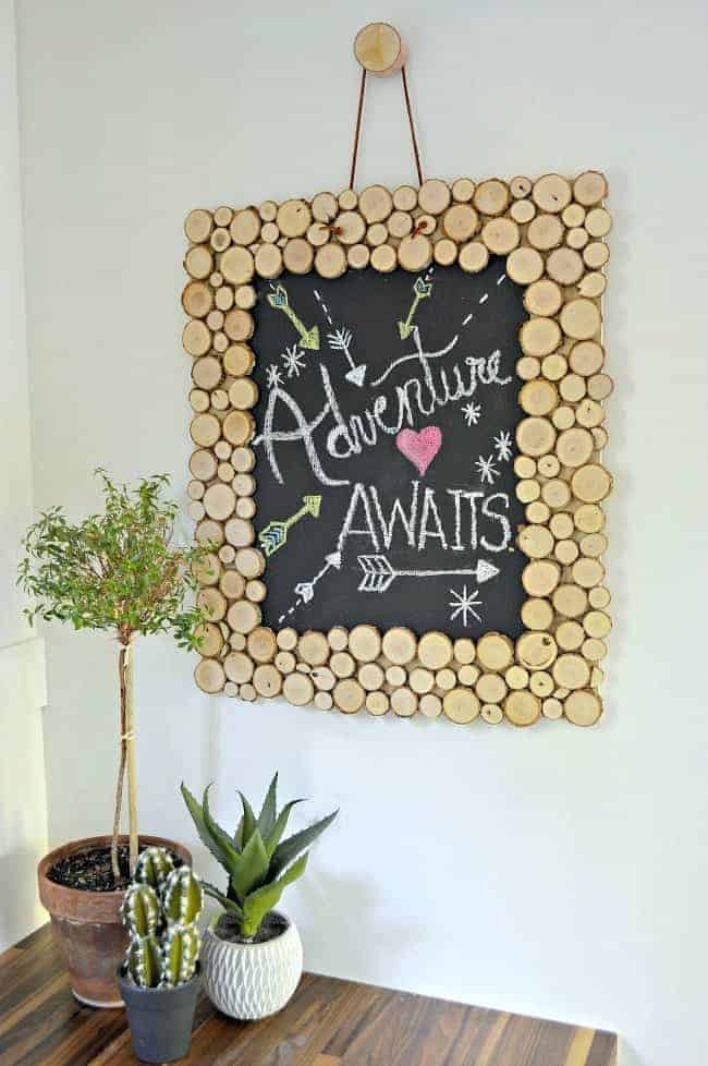Rustic Wood Slice Chalkboard hanging on white wall with 3 green plants sitting on a wood countertop.