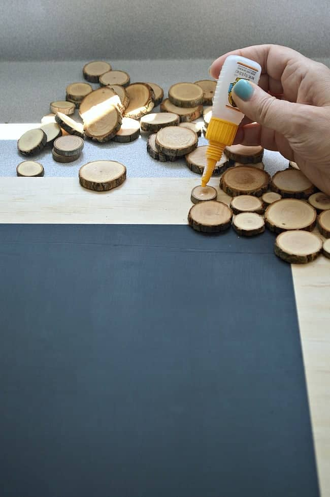 using Gorilla Glue to glue a wood round on a rustic wood slice chalkboard