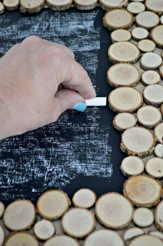 seasoning the chalkboard with chalk while making a rustic wood slice chalkboard