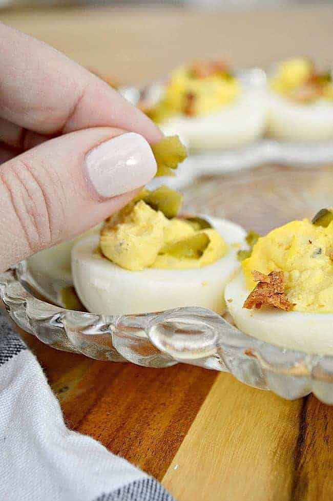 placing sweet pickle pieces on deviled eggs in egg tray