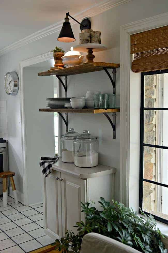 dusk with a lighted DIY wireless wall sconce hanging over open shelving in kitchen