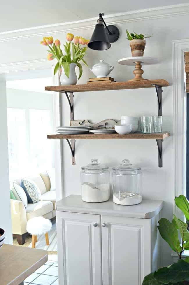 DIY wireless wall sconce hanging over kitchen open shelving with dishes and a pitcher of tulips
