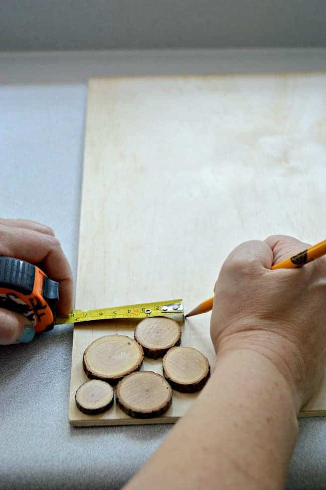 measuring border on underlayment with a measuring tape to make a rustic wood slice chalkboard