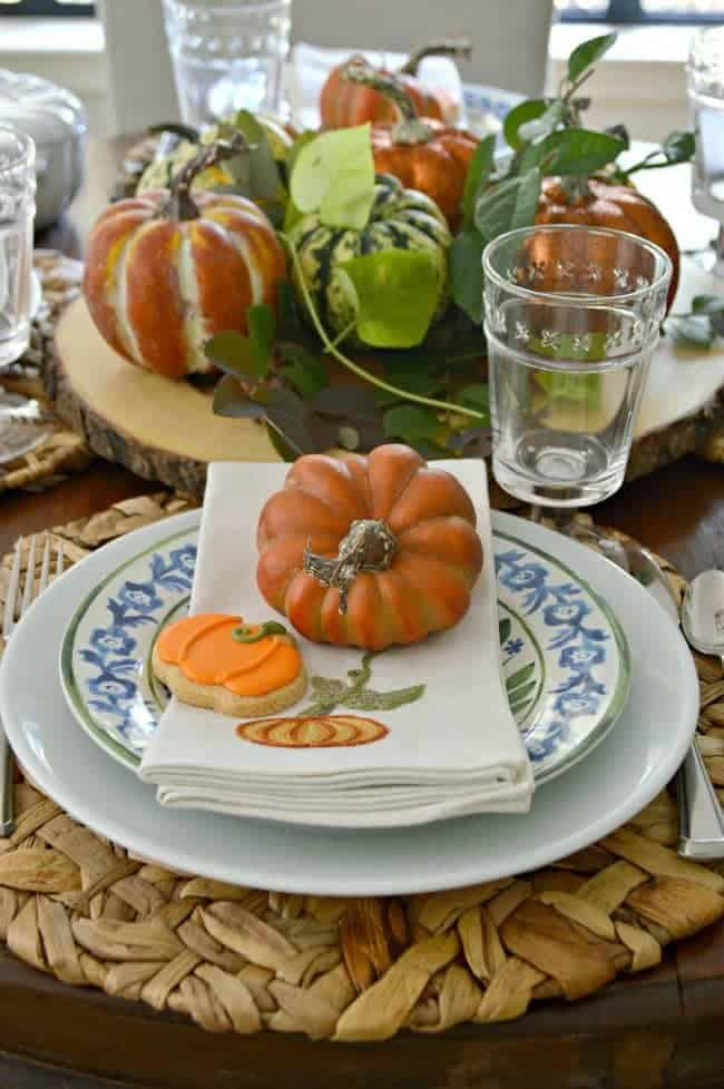 a table setting with a small faux pumpkin on pumpkin embroidered napkin for a Simple Fall Tablescape Ideas post