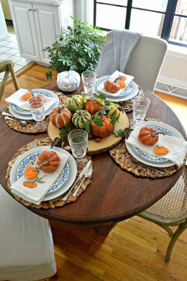 small round dining table set simply for fall with orange pumpkins and blue and white dishes for a Simple Fall Tablescape Ideas post