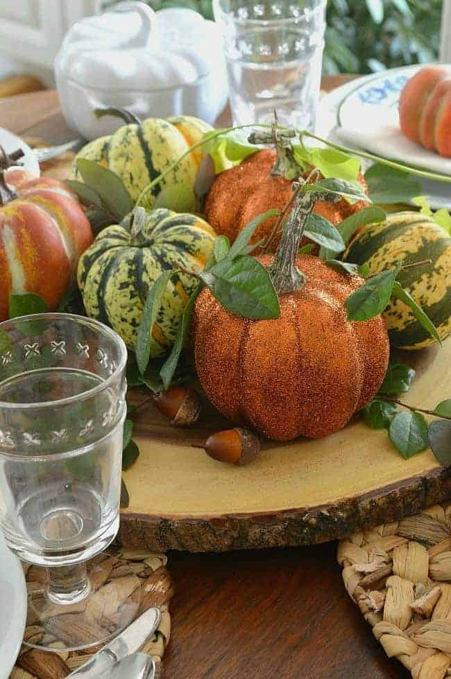 DIY glitter pumpkins, faux pumpkins and pumpkin squash on wood round in center of table.