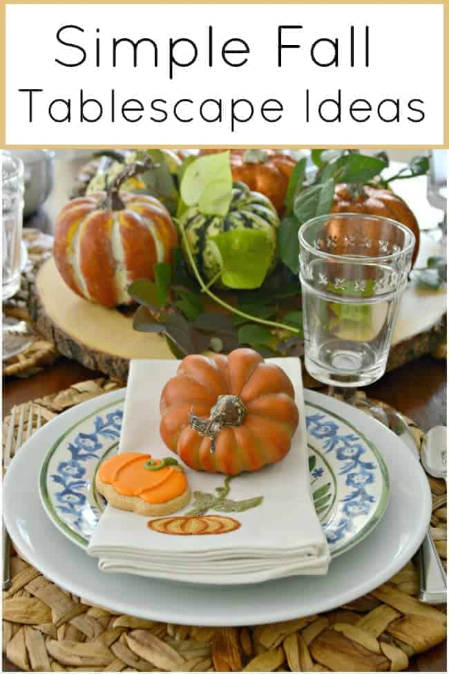 table setting with orange pumpkin on cream embroidered napkin with a pumpkin shaped cookie for a Simple Fall Tablescape Ideas post
