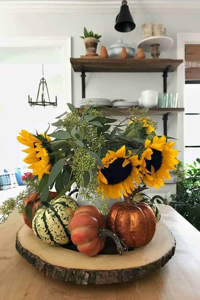 centerpiece with pitcher of sunflowers and DIY glitter pumpkins on wood round