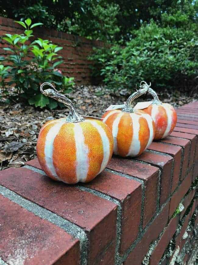 3 faux pumpkins sitting on a brick wall that will be turned into DIY glitter pumpkins