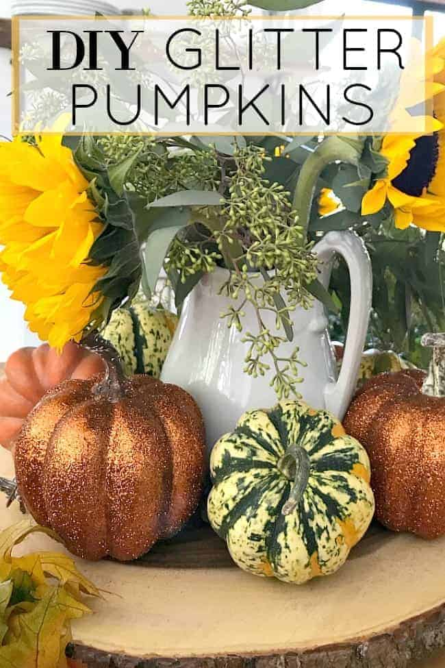 pitcher of sunflowers with glitter pumpkins in front