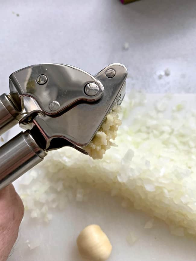 mincing garlic clove in garlic press