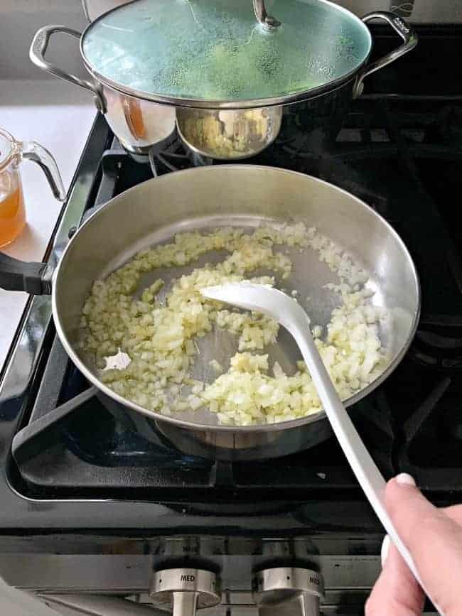 stirring saucepan on stove with garlic and onions
