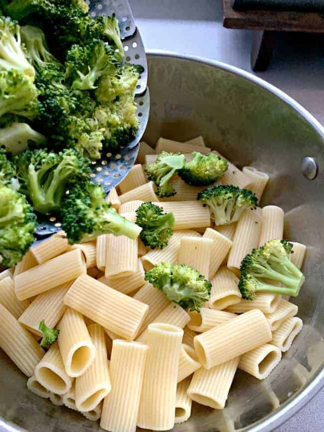 pouring steamed broccoli on to cooked noodles in pot