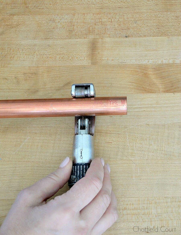 cutting a copper pipe with a pipe cutter