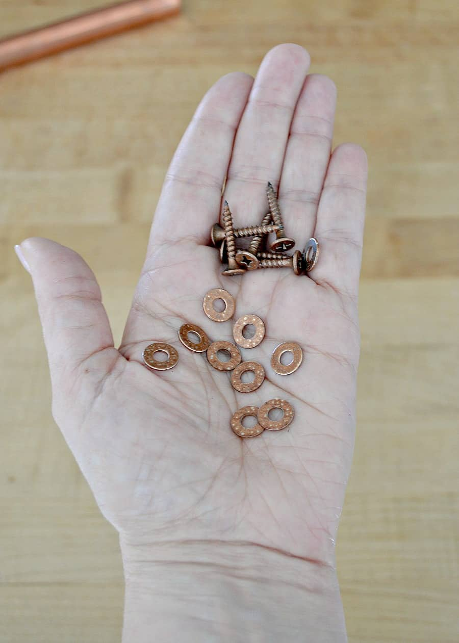 copper painted washers and screws in the palm of a hand