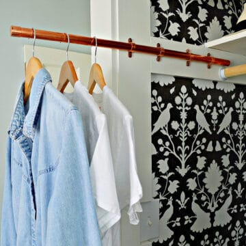 copper closet rod with clothes hanging on it
