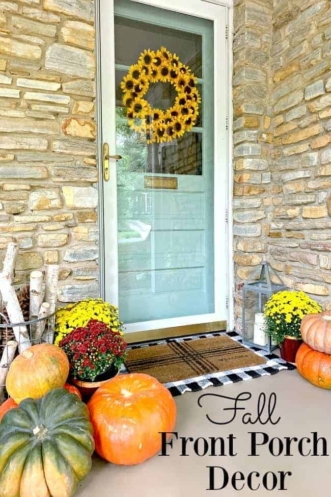 front porch fall decor with blue front door and lots of pumpkins and mums spread around