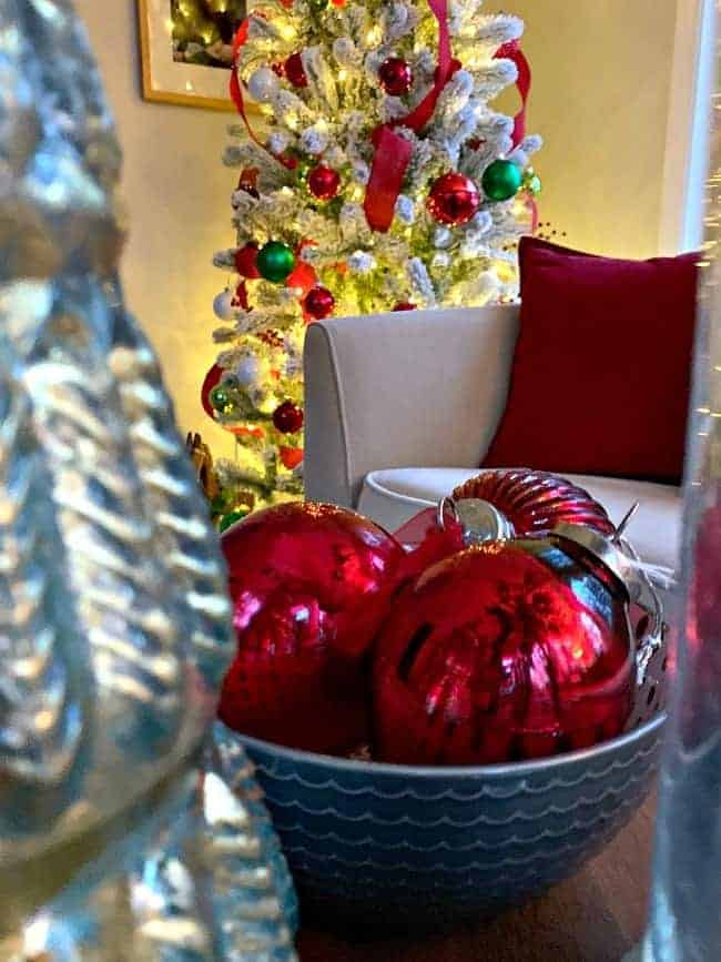 a bowl of red shiny ornaments with a flocked Christmas tree in the corner of a sunroom