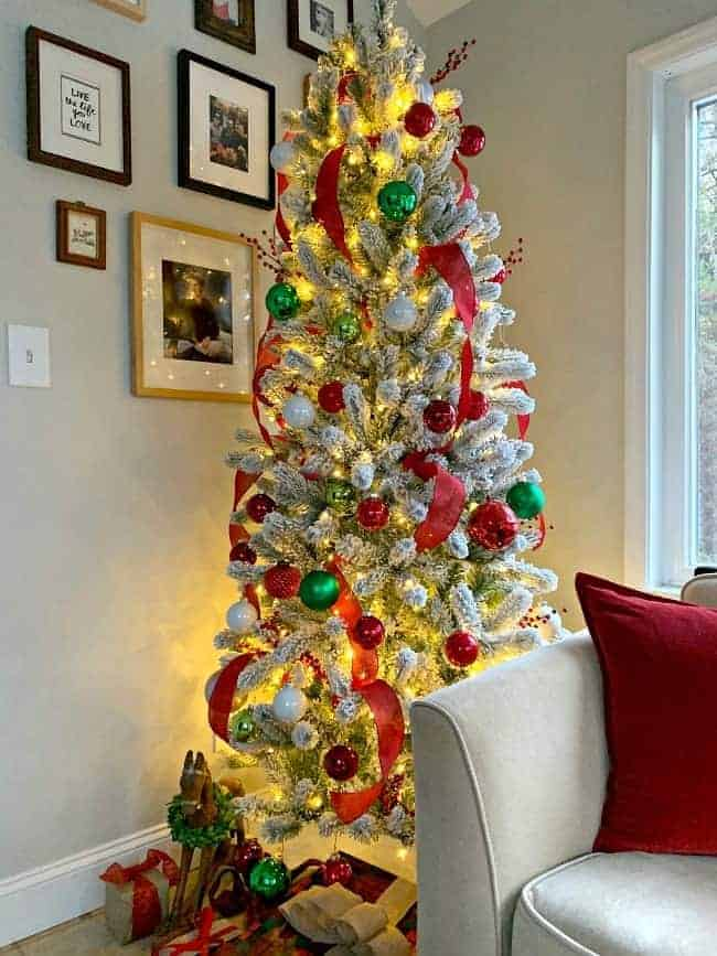 a flocked Christmas tree in the corner of a sunroom with red and green decor and presents underneath