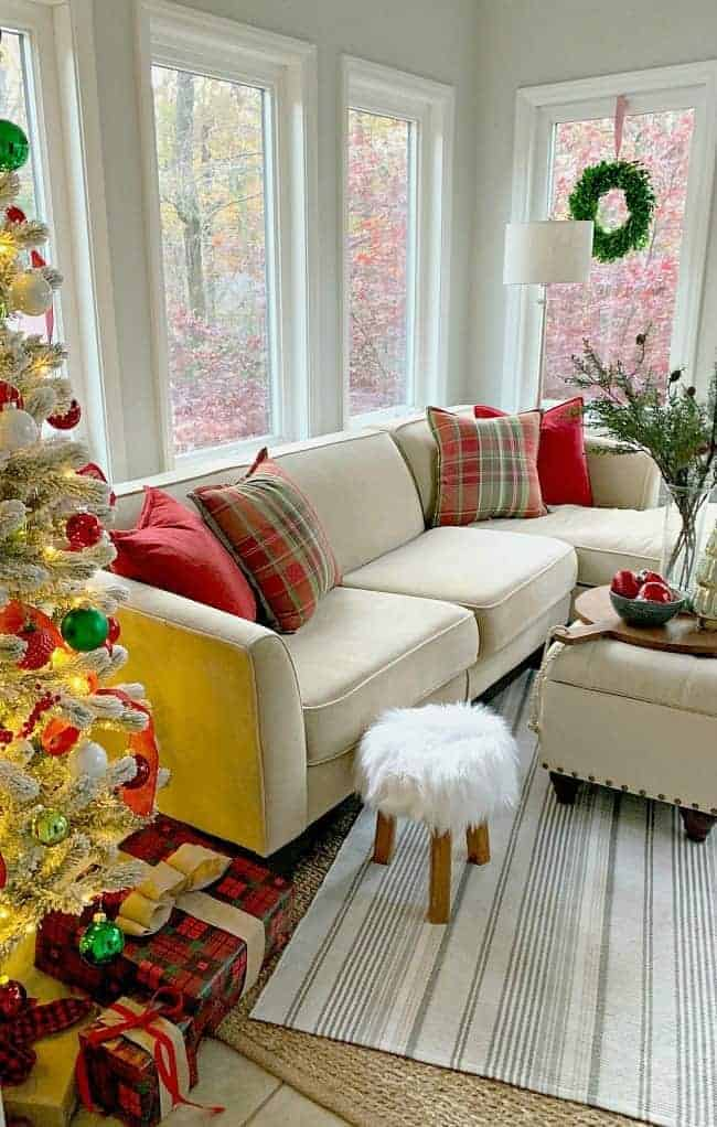 A cottage Christmas sunroom with a flocked Christmas tree in the corner of a sunroom next to a sectional sofa with red and green pillows