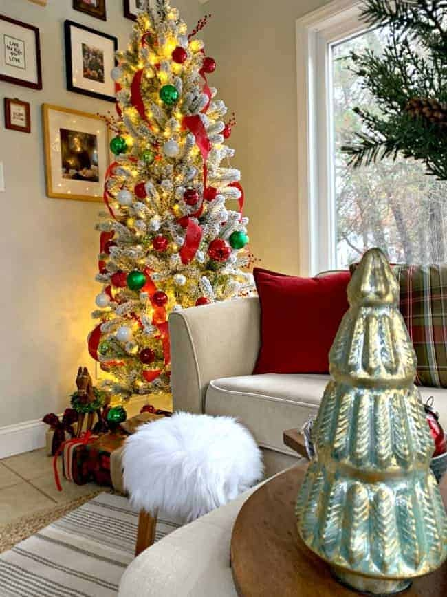a cottage Christmas sunroom with a flocked Christmas tree in the corner of a sunroom with red and green decor