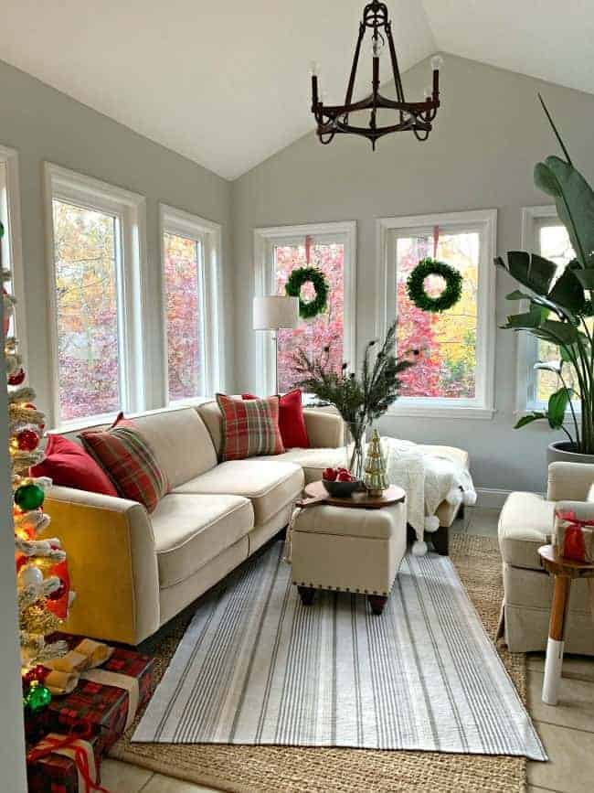 A Cozy Christmas Cottage sunroom decorated in reds and greens