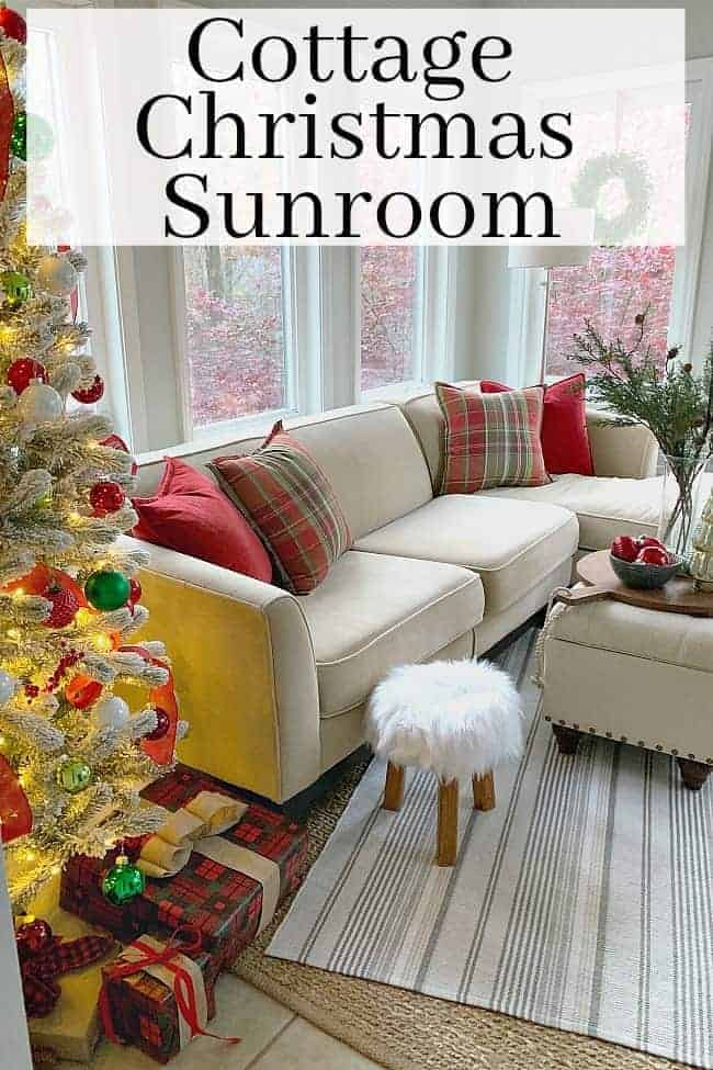A cottage Christmas sunroom with a flocked Christmas tree in the corner of a sunroom next to a sectional sofa with red and green plaid pillows