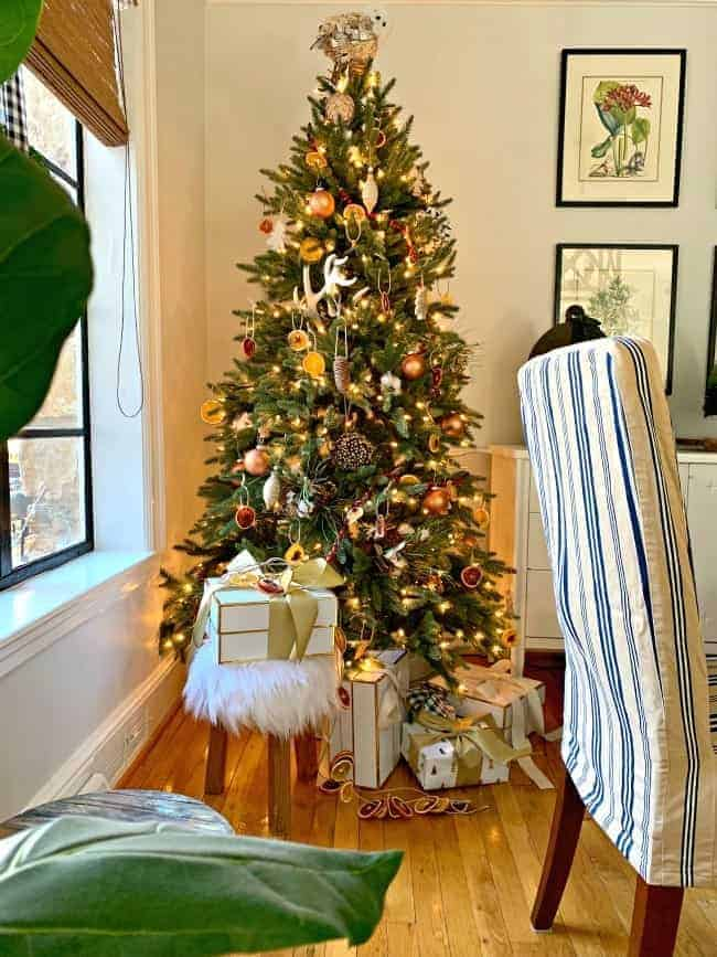 A Rustic Christmas Tree in a corner with wrapped presents and a fur stool underneath it.
