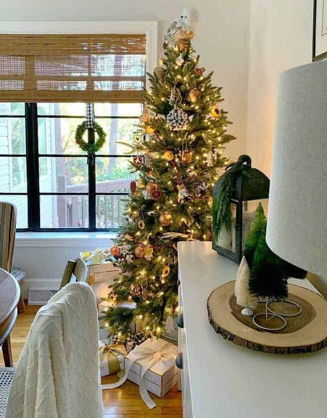 A Rustic Christmas Tree in a dining room corner with gifts underneath