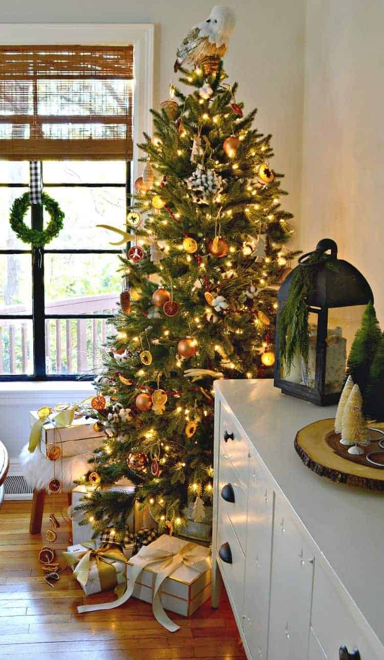 A Cozy Christmas Cottage dining room with a nature inspired Christmas tree in the corner by the window