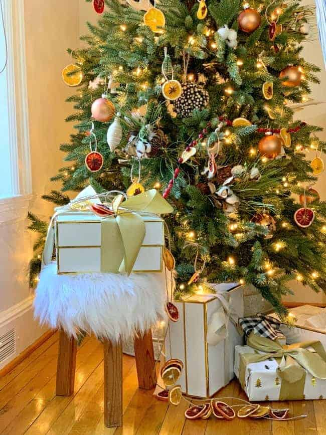 A Rustic Christmas Tree with a fur covered stool under it and wrapped gifts