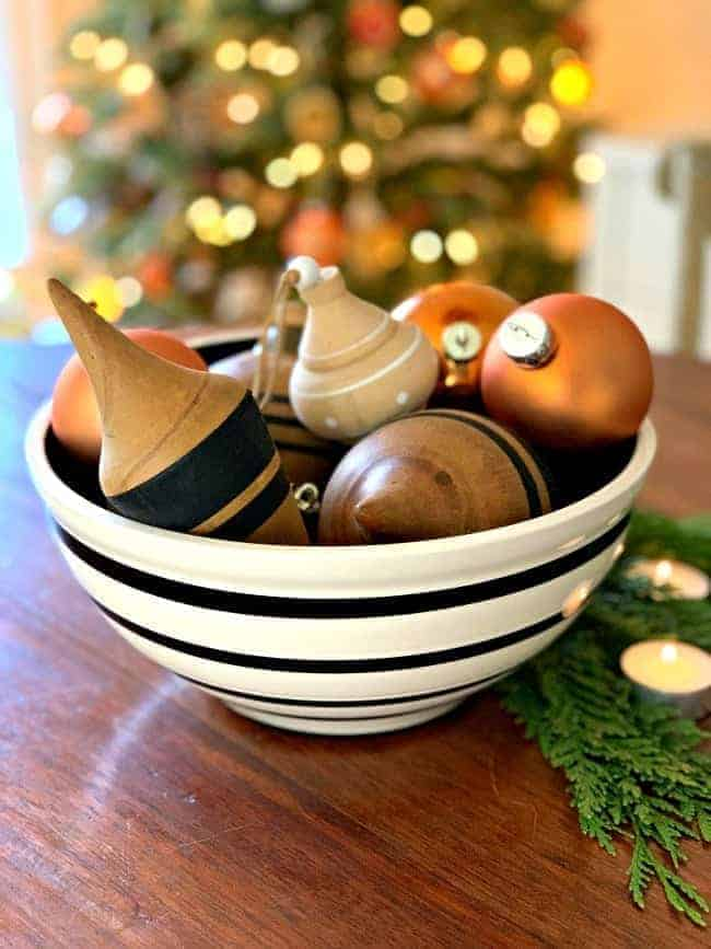 black and cream bowl on wood table with wood ornaments and burnt orange glass balls
