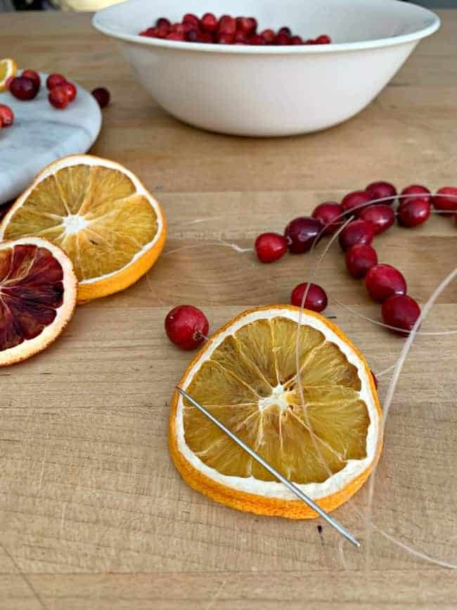 making a DIY Christmas garland with dried orange slices, cranberries and a needle and fishing line