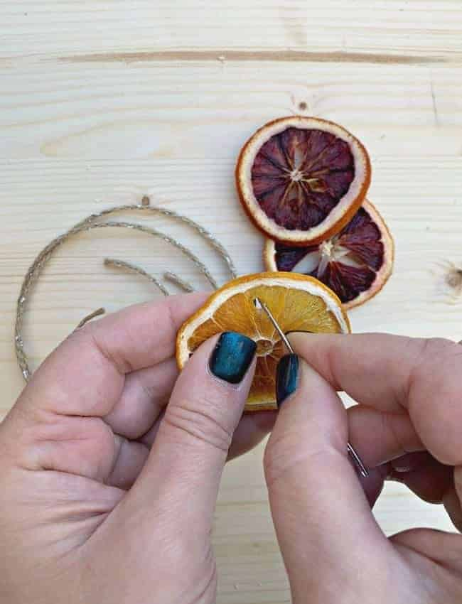 using needle to poke hole in dried orange slice ornament