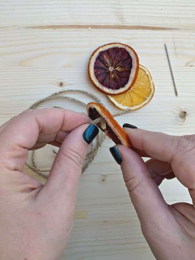 threading thin jute twine through hole in dried blood orange slice