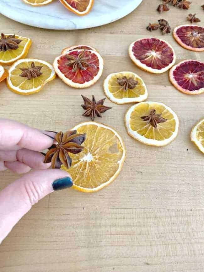 glueing star anise on dried orange slice with more dried orange slices scattered around