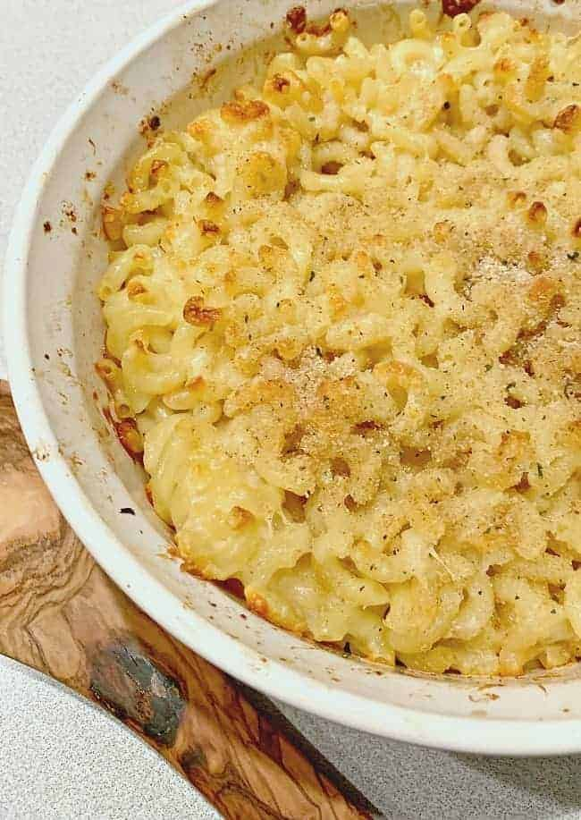 baked homemade cheesy mac and cheese in baking dish with wooden spoon next to it