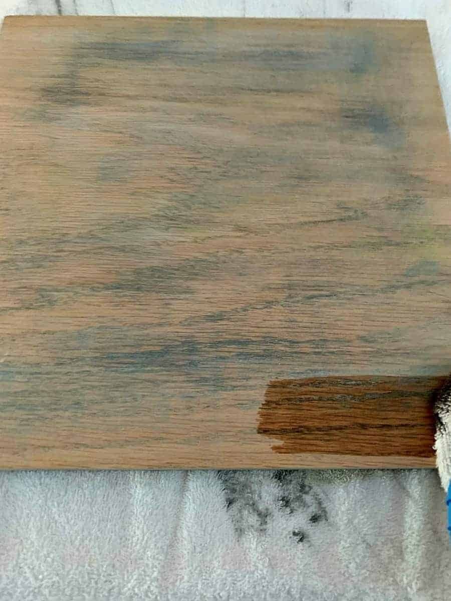 applying wood stain to piece of oak wood