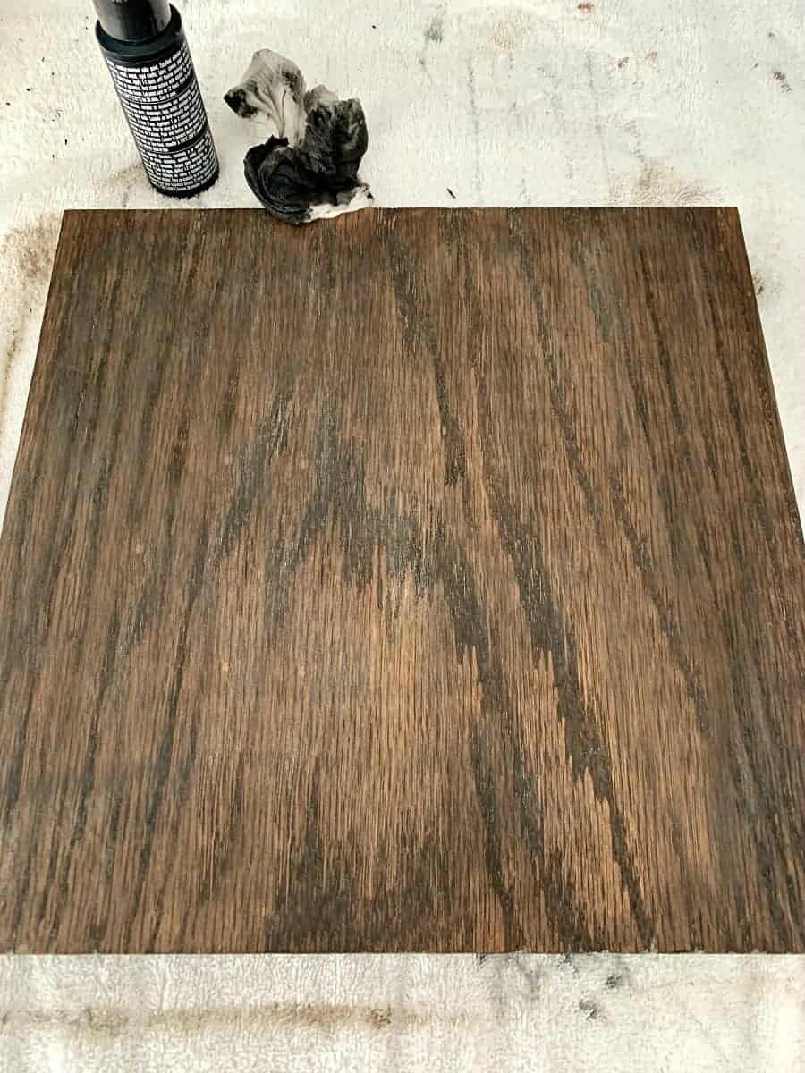 piece of oak wood after black paint is applied over stain