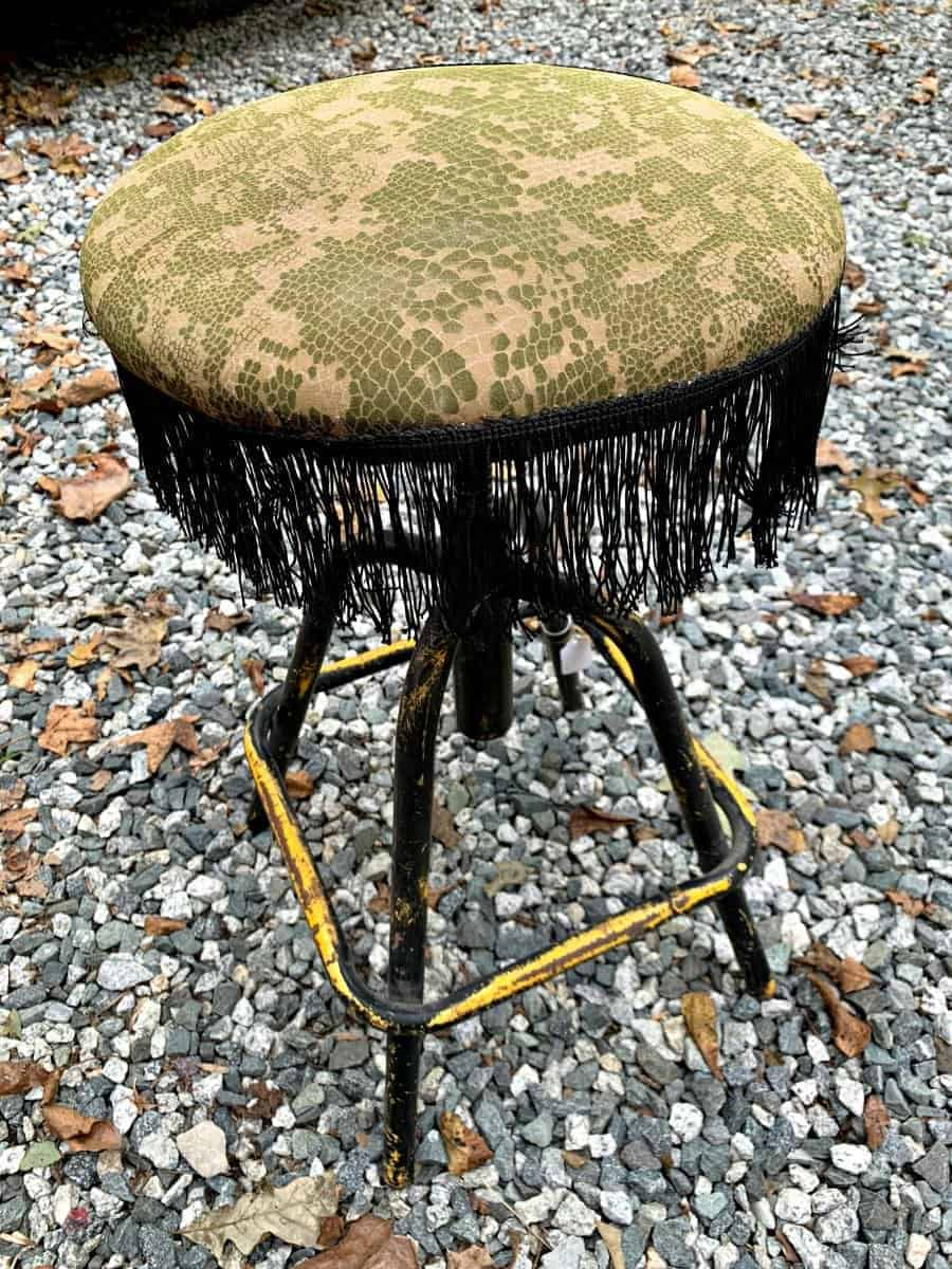 old thrifted metal stool with black fringe on seat