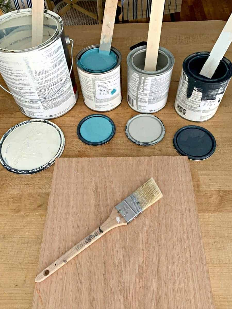 4 open cans of paint and a piece of oak wood with a paintbrush on top